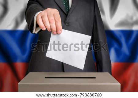 Election in Russia - voting at the ballot box. The hand of man putting his vote in the ballot box. Flag of Russia on background.