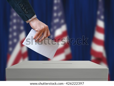 Shutterstock Election in United States of America. Voter holds envelope in hand above vote ballot. USA flags in background. Democracy concept.