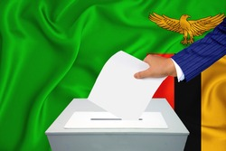 Elections in the country - voting at the ballot box. A man's hand puts his vote into the ballot box. Flag Zambia on background.