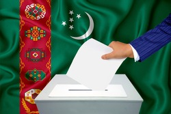 Elections in the country - voting at the ballot box. A man's hand puts his vote into the ballot box. Flag turkmenistan on background.