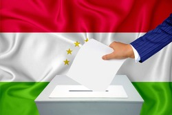 Elections in the country - voting at the ballot box. A man's hand puts his vote into the ballot box. Flag Tajikistan on background.