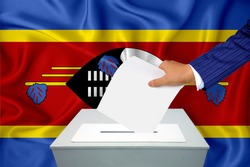 Elections in the country - voting at the ballot box. A man's hand puts his vote into the ballot box. Flag swaziland on background.
