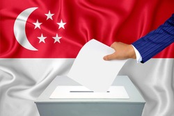 Elections in the country - voting at the ballot box. A man's hand puts his vote into the ballot box. Flag Singapore, Singaporean on background.