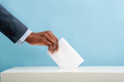 Elections in USA 2020. African american man putting an empty ballot in election box over blue background, copy space