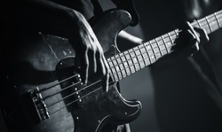 Electric bass guitar player hands, live music theme, black and white photo
