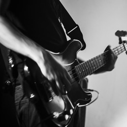 Electric bass guitar player, live music theme. Retro stylized square black and white photo