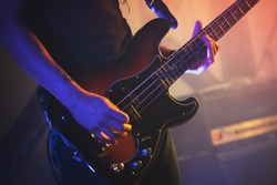 Electric bass guitar player on a stage, closeup photo with soft selective focus