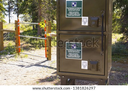 Electric bear fence around tenting area  and bear-resistant food storage lockers at a Yukon campsite, Canada. #1381826297