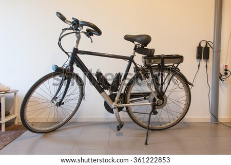 Electric bicycle in a garage, charging the battery #361222853