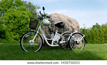 Electric bicycle on the green grass with stone background on sunny summer day. Shot from the side. A lot of natural lighting. The view of the e motor, power battery gear, hamlet and gloves. #1430750255