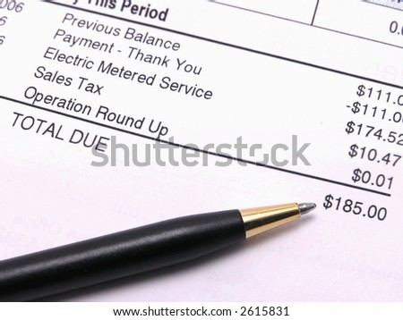 Electric bill with pen pointing towards amount due