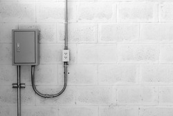 electric box on concrete wall with steel tube and plug, black and white