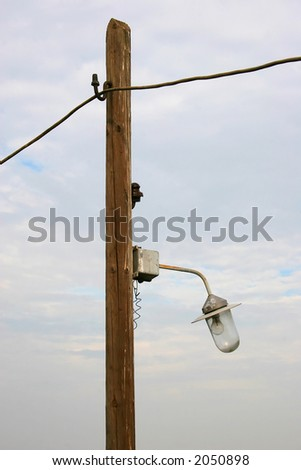 Electric bulb , post , wire and sky.