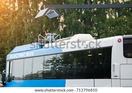 Electric bus at a stop is charged by wireless charging