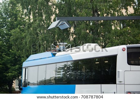 Electric bus at a stop is charged by wireless induction charging #708787804
