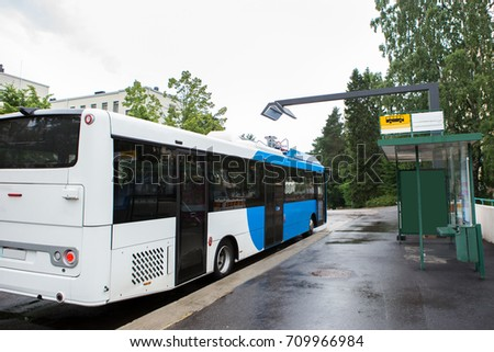 Electric bus at a stop is charged by wireless induction charging #709966984