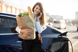 Electric car charging concept. Portrait of young likable pretty businesswoman with bag of fresh food, standing at the charging station and talking phone while waiting for her car charging