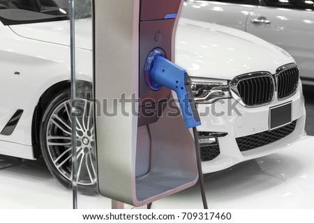 Electric car charging on parking lot with electric car charging station on city street. Close up of power supply plugged into an electric car being charged.