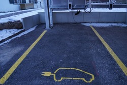 Electric car charging station on a public parking place. It is marked with electric car pictogram with electric plug instead of an exhaust.