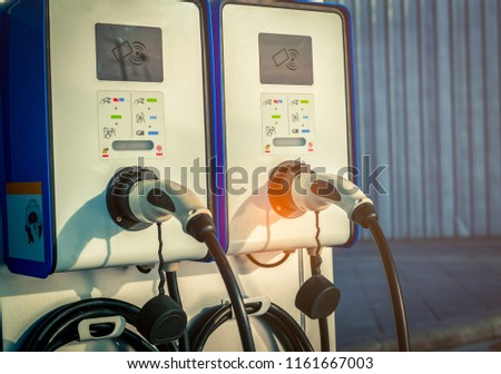 Electric car charging station. Plug for vehicle with electric motor. Coin-operated charging station. Clean energy power. Commercial charging station. Charging point. Infrastructure policy.  #1161667003