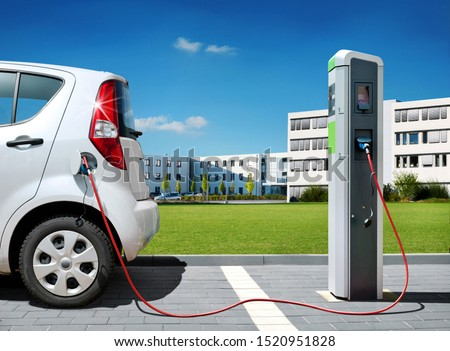 Electric car on charging spot in front of architecture office buildings - Car sharing commuter charging station Stockfoto ©