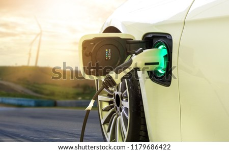 Electric car or EV car charging in station on blurred of sunset with wind turbines in front of car on background.  Eco-friendly alternative energy concept