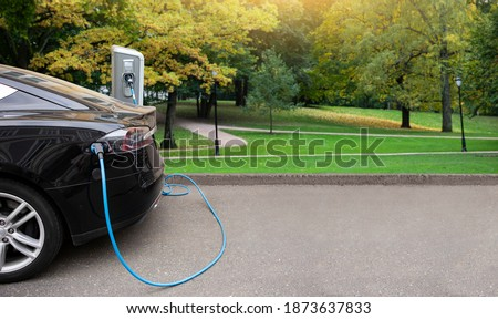 Electric car with a charging station on a background of city park