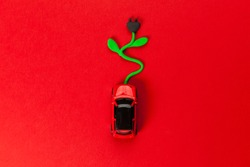 Electric car with socket for charging battery on red background. Eco vehicle, clean energy alternative future.
