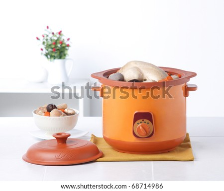 Electric casserole pot with chicken and spices isolated in the kitchen interior