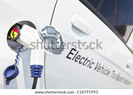 "Electric charging nozzle inserted into electrical vehicle's charging plug. Selective focus on the nozzle. Part of the ""Eco-vehicles"" collection set."