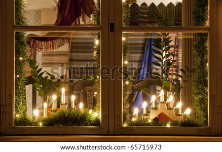 Electric Christmas candles and decorations behind a wooden window - stock photo