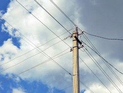 Electric concrete pillar against a blue sky. Illustration on the theme of electricity supply and rising prices. The wires cross against a background of fluffy white clouds. Rural electrification