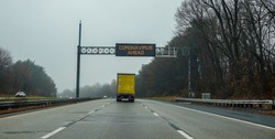 Electric digital warning sign above a truck on a highway that says Coronavirus Ahead