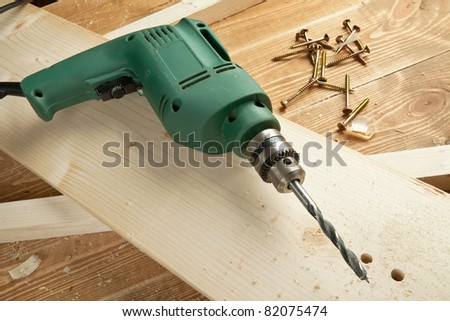 Electric drill on wooden board