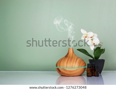 Photo of  Electric Essential oils Aroma diffuser, oil bottles and flowers on light green surface with reflection.