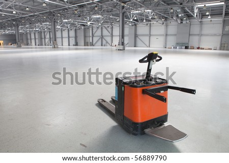 Electric forklift in large modern storehouse with some goods