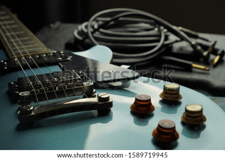 Electric guitar and guitar amplifier with jack cable, close up of guitar fingerboard with guitar amplifier background, cable jack and amplifier.