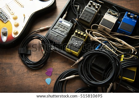 Electric guitar and guitar audio processing effects on a studio floor. Electric guitar and stomp box type effectors and cables on studio floor. Intentionally shot with low key tone.