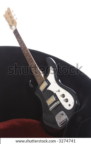 Electric guitar at an angle on red velour chair, white background