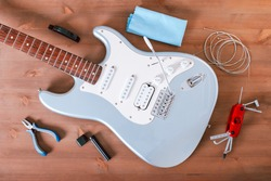 Electric guitar body, new strings and various guitar tools for maintenance and restringing on wooden table top