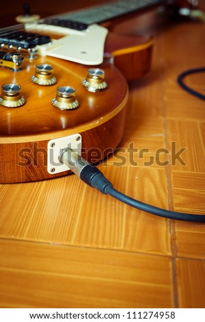 Electric guitar honey burst color on floor with jack cable