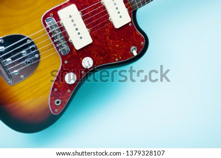 Photo of Electric guitar on blue background. Free space for text