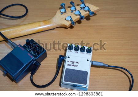 Electric guitar stomp box effectors and guitar neck,wooden background.