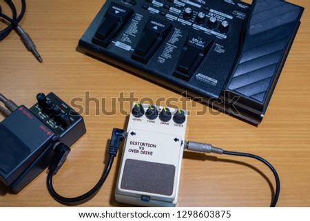 Electric guitar stomp box effectors and multi effect,wooden background.