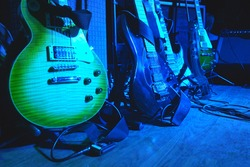 Electric guitars before the concert stand on stage on stands under the light of spotlights.