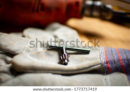 Electric Hand Drill Chuck Wrench Tool Part Drill Chuck Keys over industrial gloves and drill in the background