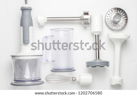 Electric hand mixer. Set of nozzles and  containers for blender on white background. Top view, flat lay