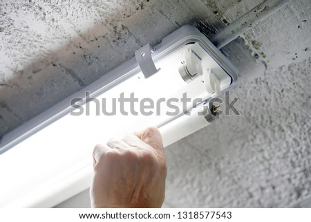 Electric hands changing ceiling fluorescent lamp. The concept of repair and service.