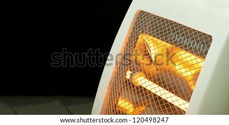 Electric heater with halogen coils close up. Dark copy spice