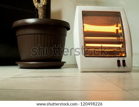 Electric heater with halogen coils. Flower pot and heater on marble slabs